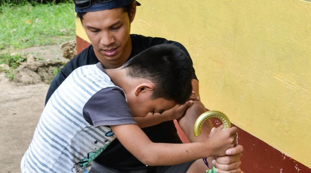 A male intern at Projects Abroad assisting a child with walking and straightening his legs whilst on his physiotherapy internship in the Phillippines.